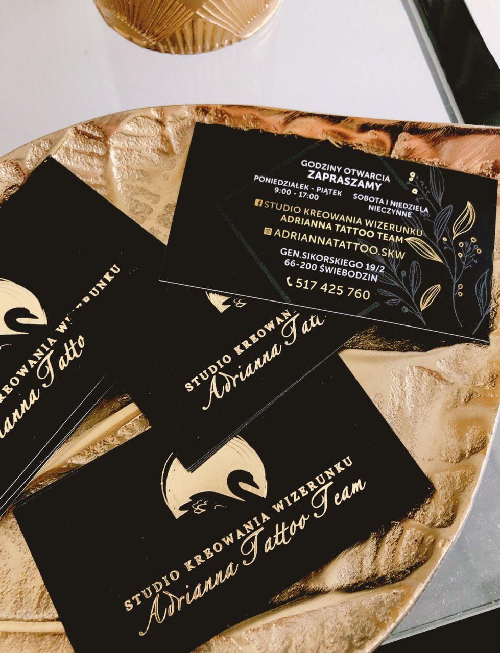 wizytówki ze złoconym logo Studio Kreowania wizerunku Adrianna Tattoo Team