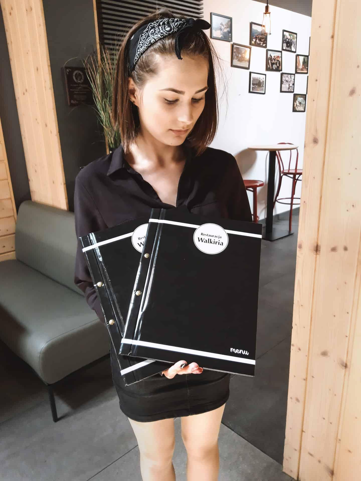 menu trzymane przez kelnerkę w restauracji Walkiria